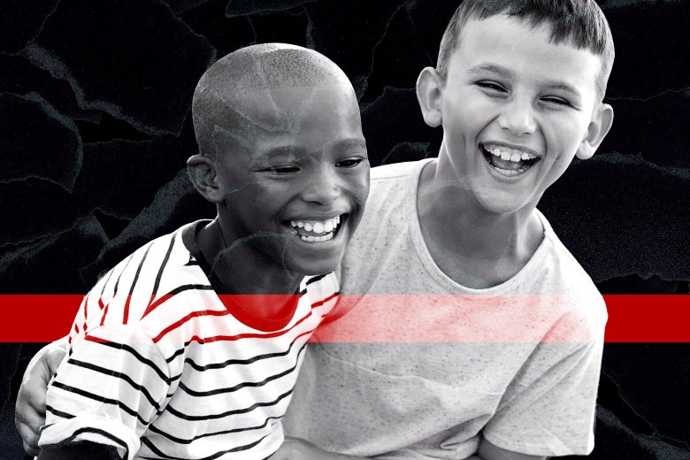 A young Black boy and a young white boy laugh together.