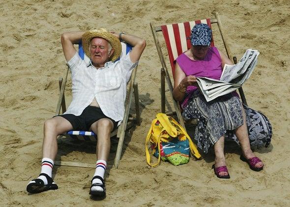 A couple sits on the beach.