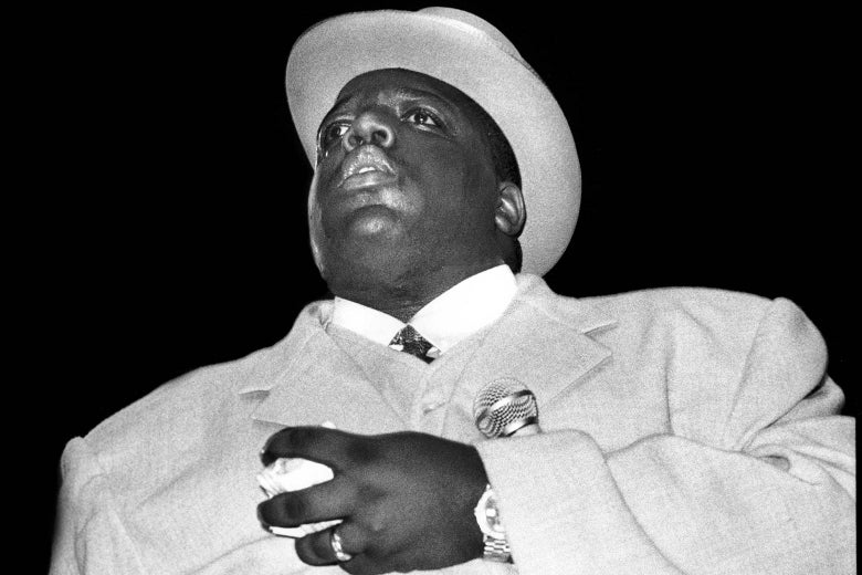 The Notorious B.I.G., in a coat and top hat, holding a microphone in his arm
