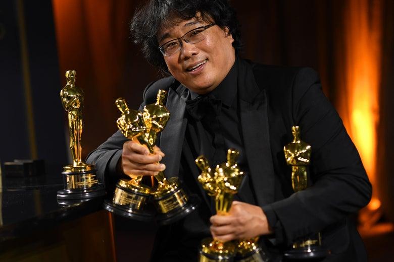 Bong Joon-ho poses with an armful of Oscars.
