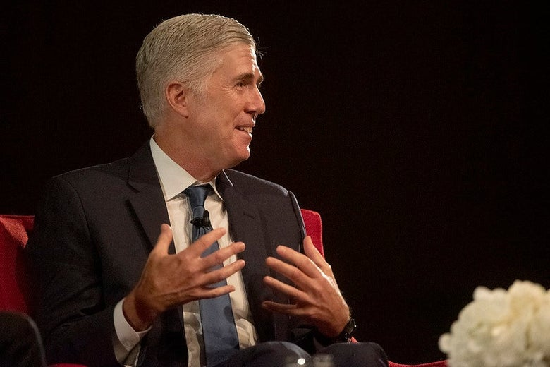 Neil Gorsuch, seated onstage, gesticulates and grins.
