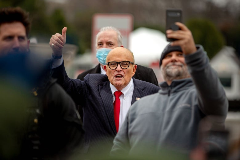 A Trump supporter snaps a selfie with Rudy Giuliani.