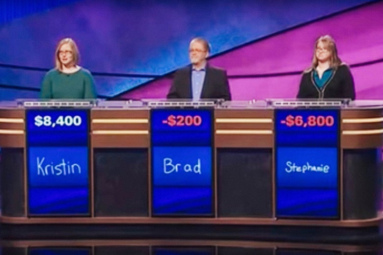 Three Jeopardy! contestants stand at their tables, with their scores and names displayed below.
