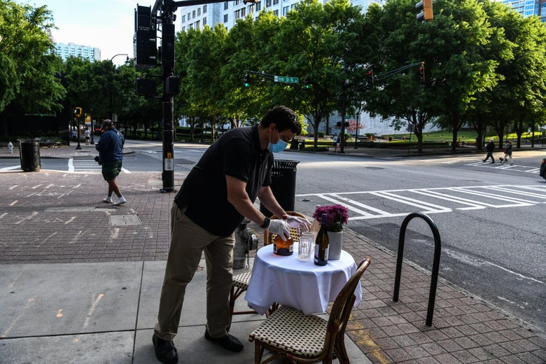 A man decorates a bistro table outside his restaurant amid the novel coronavirus pandemic in Atlanta, Georgia on April 27, 2020. - Some Georgia restaurants reopened on April 27, 2020 for limited dine-in service as the state loosened more coronavirus restrictions. (Photo by CHANDAN KHANNA / AFP) (Photo by CHANDAN KHANNA/AFP via Getty Images)