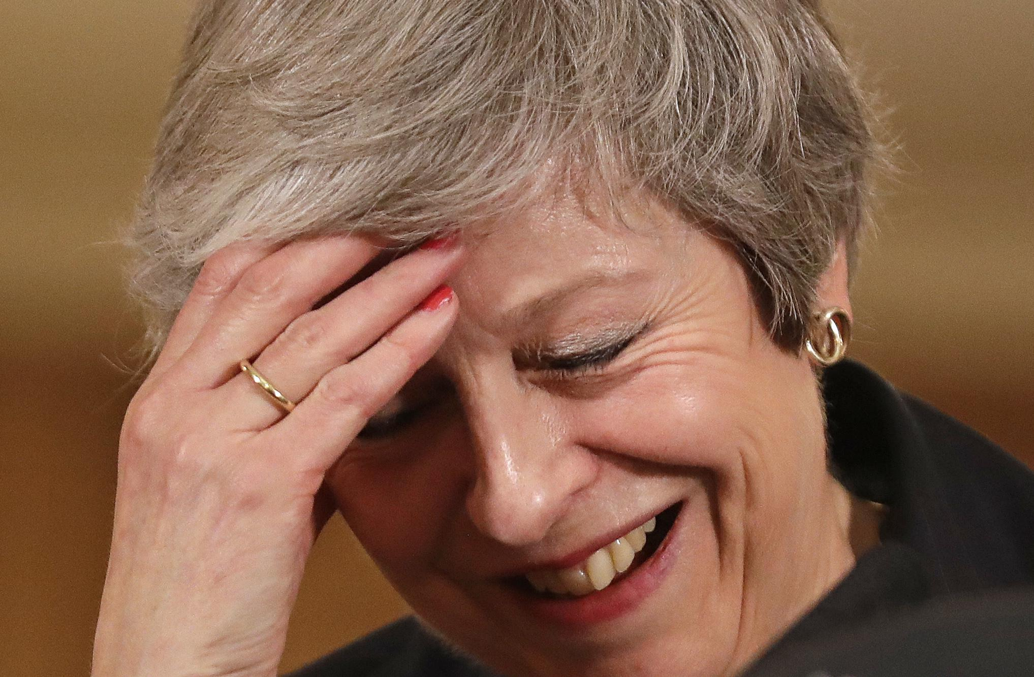Britain's Prime Minister Theresa May laughs as she speaks during a press conference inside 10 Downing Street on November 15, 2018.