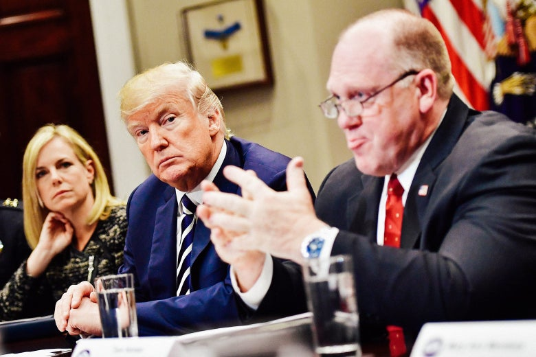 Kirstjen Nielsen, Donald Trump, and Thomas Homan at a conference table.