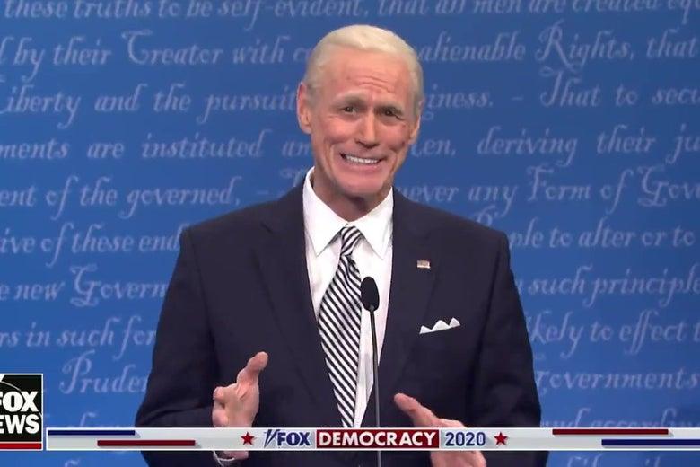 Jim Carrey as Joe Biden, standing in front of a debate podium, smiling broadly.