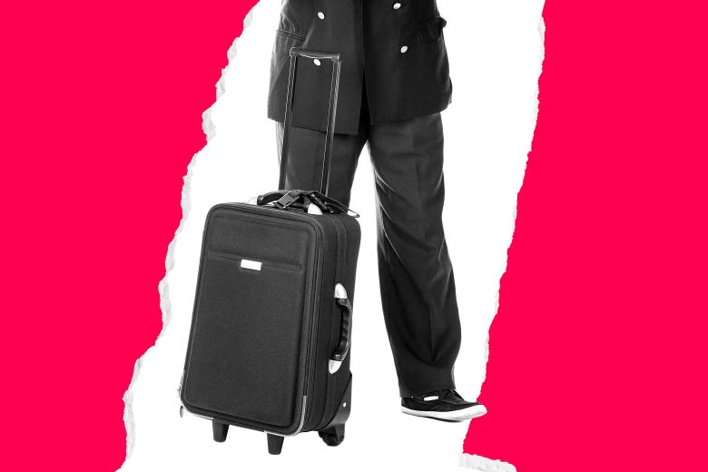 A man stands behind a suitcase.