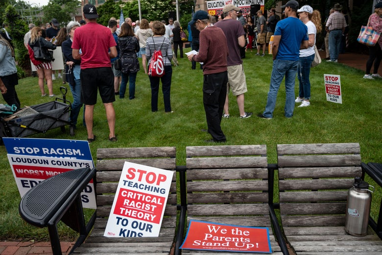 """Signs that read """"stop teaching critical racist theory to our kids"""" are seen on a bench during a rally against """"critical race theory"""" being taught in schools at the Loudoun County Government center in Leesburg, Virginia on June 12, 2021."""