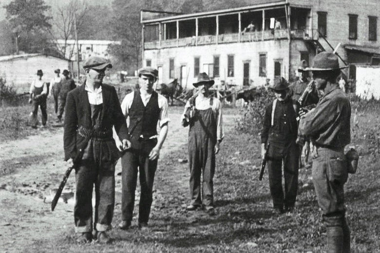 Coal miners and federal troops with weapons stand outside a building.
