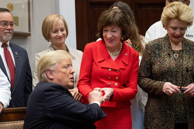 President Donald Trump presents Maine Sen. Susan Collins with a pen after signing bills intended to lower prescription drug prices during a ceremony on Oct. 10, 2018, in Washington.