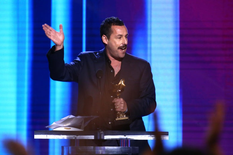 Adam Sandler stands at a podium holding his Independent Spirit Award.