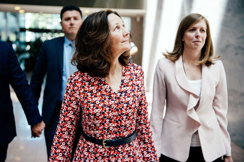 Gina Haspel walks through a Senate office building while wearing a flowery red dress.
