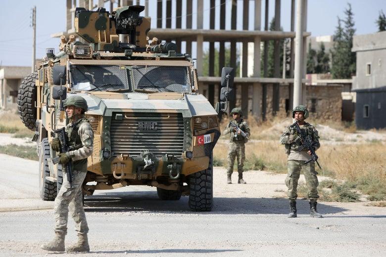 Turkish soldiers patrol a northern Syrian Kurdish town with tank.