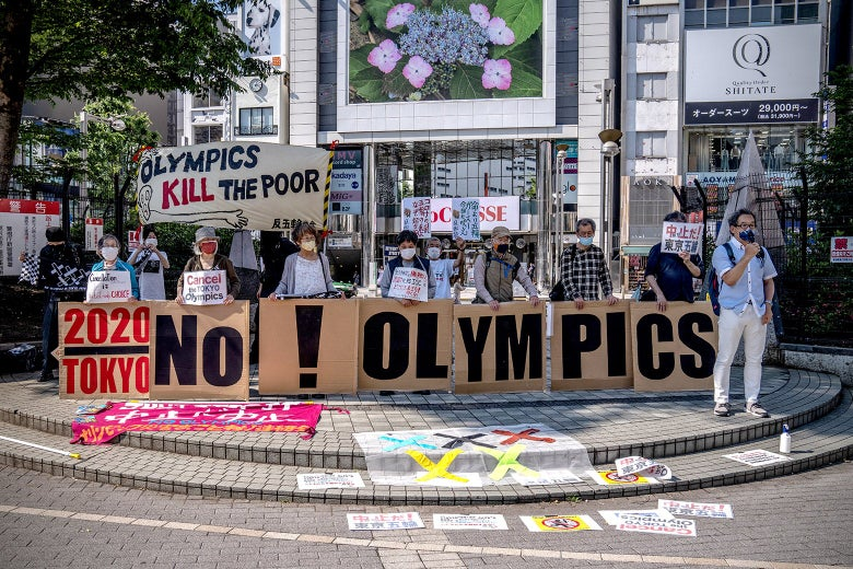 """Protesters hold signs that spell out """"No! Olympics."""""""