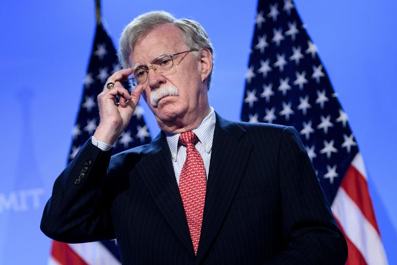 John Bolton adjusts his glasses in front of two American flags.