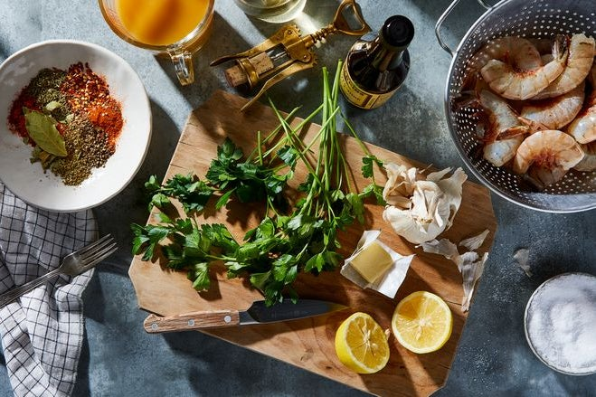 On a wooden cutting board: a bowl full of spices and bay leaf, a cup full of stock, a bunch of parsley, a bottle of Worcestershire sauce, raw shrimp in a colander, salt, garlic, butter, and a halved lemon.
