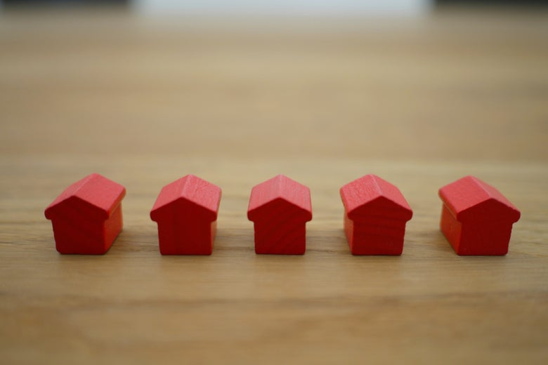 Five small red toy houses lined up on a wooden counter.