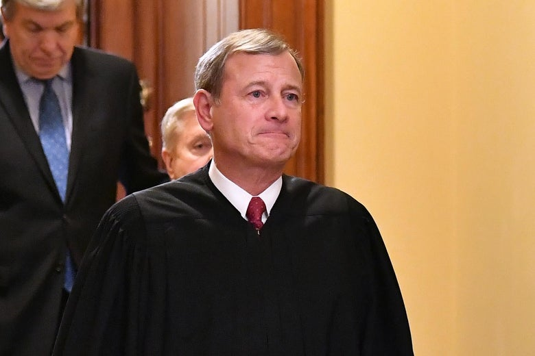 John Roberts, in robes, walks out of a room.