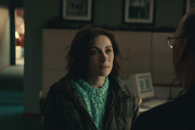 Benanti sits in a coat and sweater in an office. Behind her, an early-2000s computer.