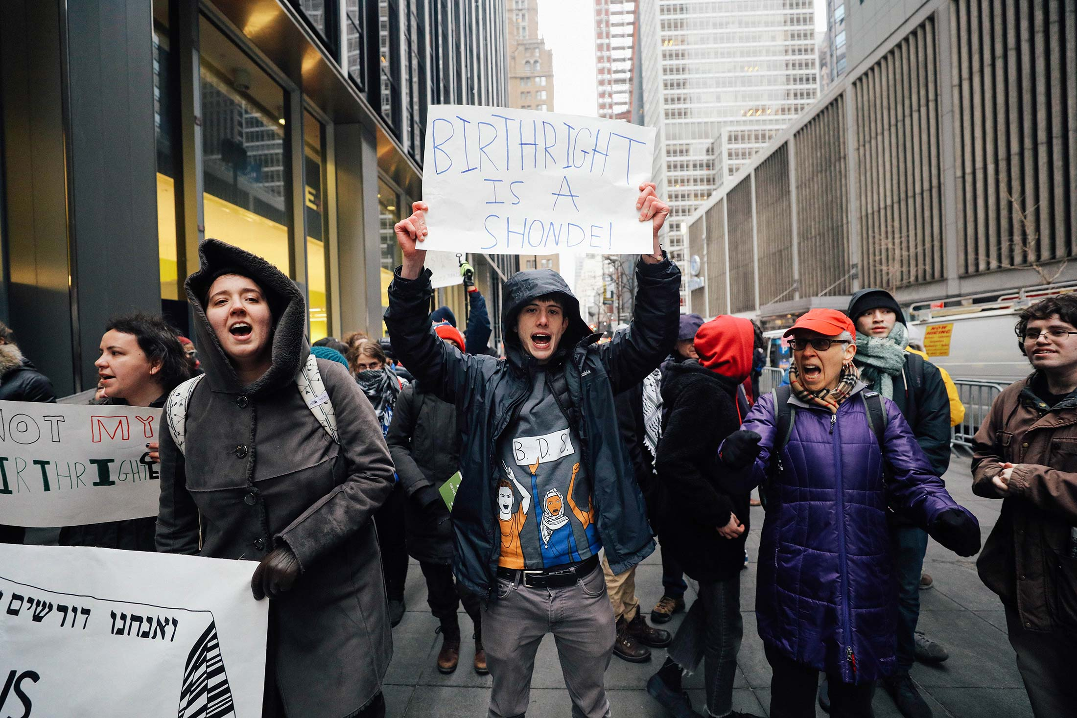 "A young man wearing a hooded black jacket holds up a sign saying ""BIRTHRIGHT IS A SHONDE"" in a crowd of protesters in midtown Manhattan."