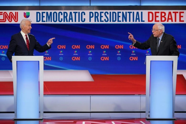 Biden and Sanders point at each other from across the debate stage.
