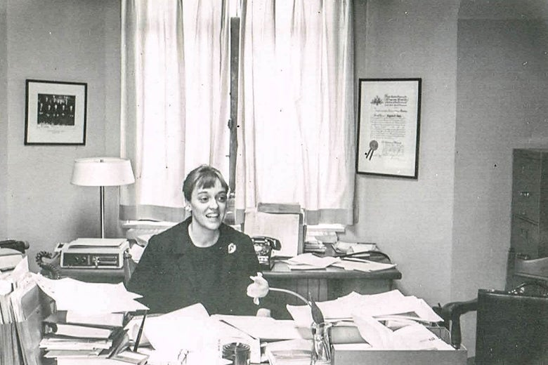 Virginia Davis Nordin sits at a desk piled high with papers.