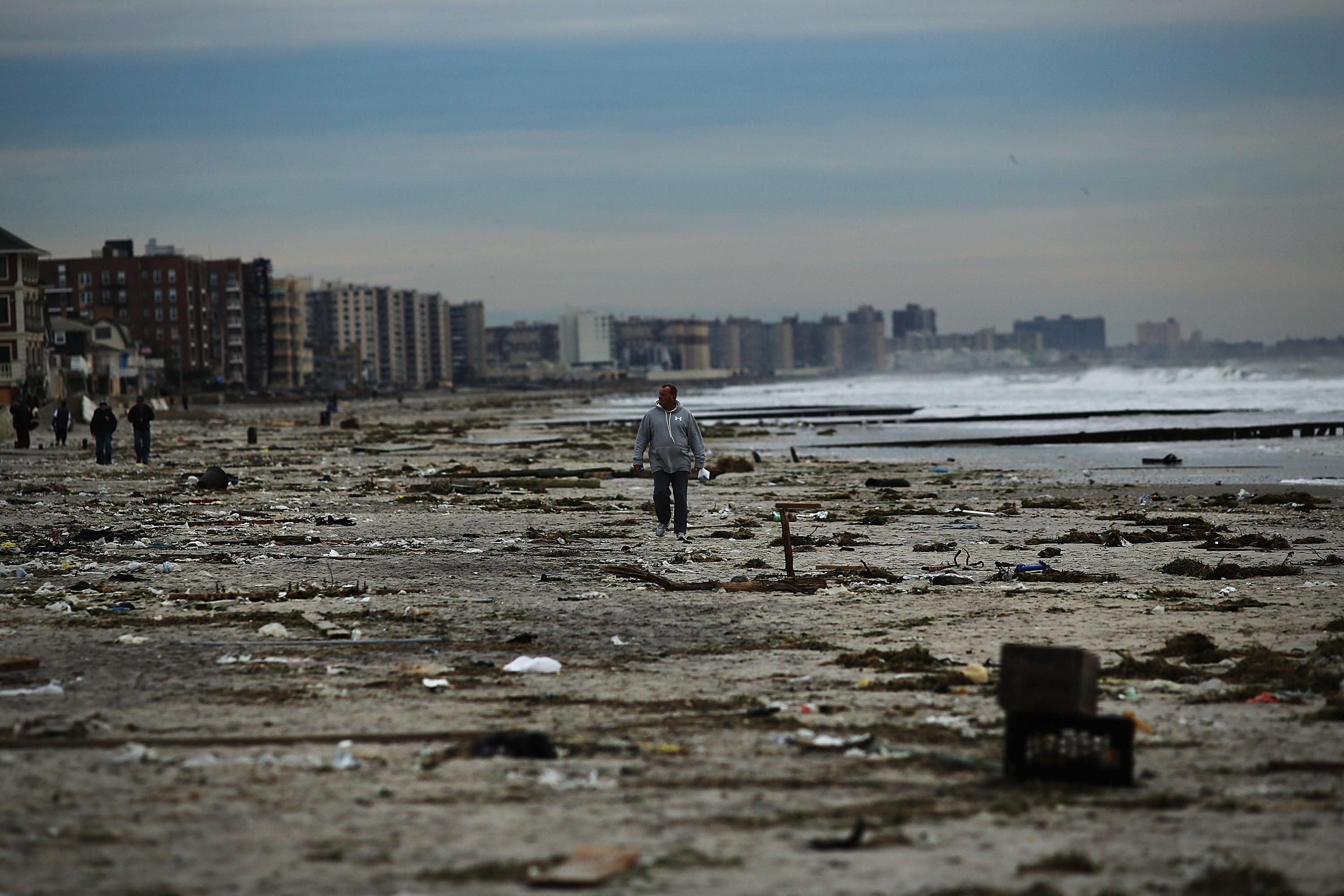 A man walks along the beach in the heavily damaged Rockaway neighborhood, in Queens where a large section of the iconic boardwalk was washed away on November 2, 2012 in New York.