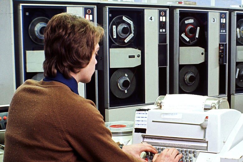 A man types on a big old-fashioned mainframe computer.