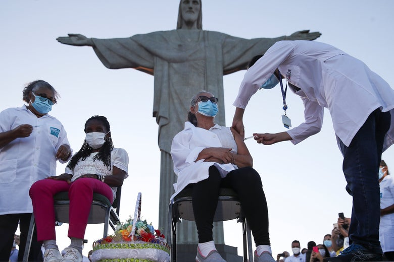 woman getting vaccine below Christ the Redeemer statute
