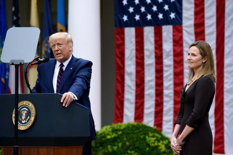Trump at a podium with Amy Coney Barrett standing off to the side smiling.