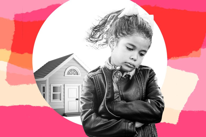 A young girl with her arms folded, looking unhappy, standing outside a small house.