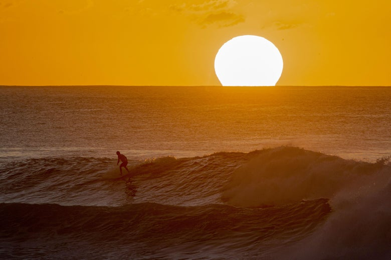 A surfer rides a wave as the sun sets on the horizon.