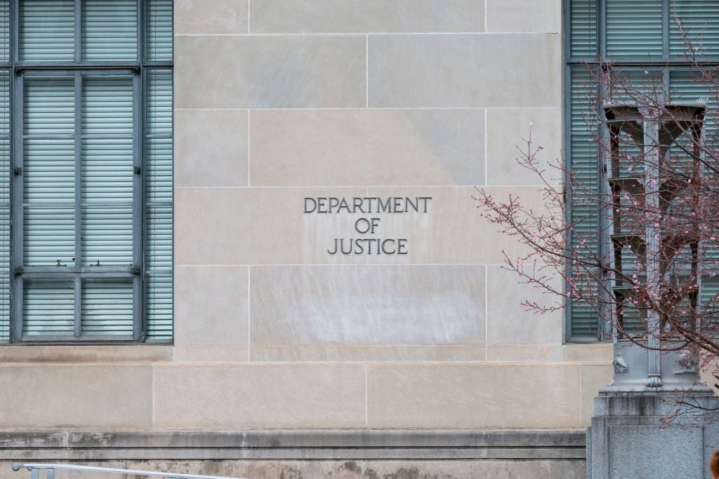 """A brick wall between large windows with the words """"Department of Justice"""" etched into it."""