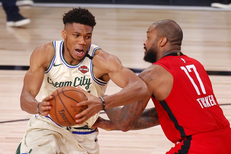 Giannis Antetokounmpo goes for a shot while P.J. Tucker defends.