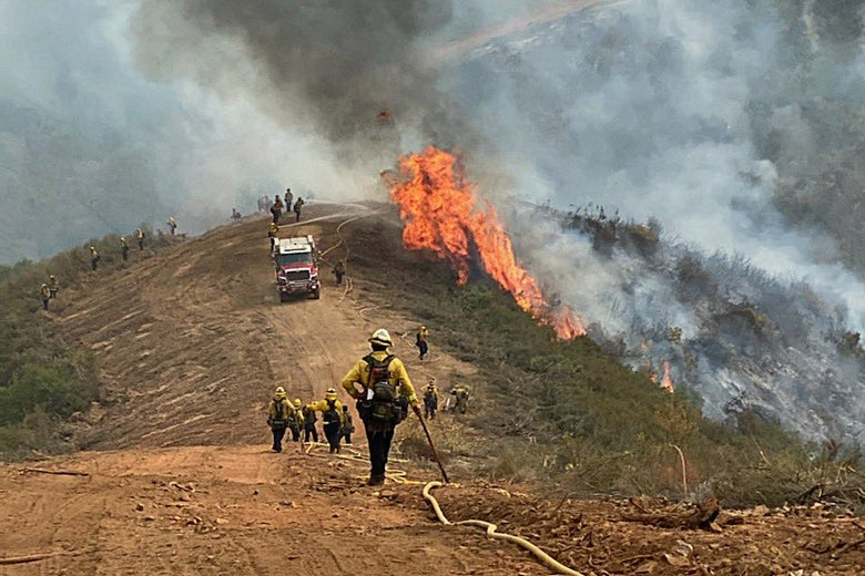 Firefighters standing near a fire, surrounded by smoke