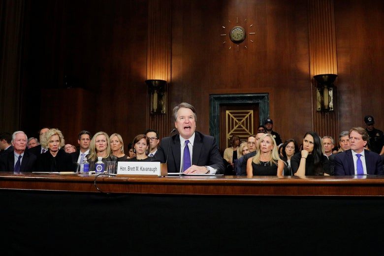 Kavanaugh yelling. Behind him, women seated in the front row look disgusted.