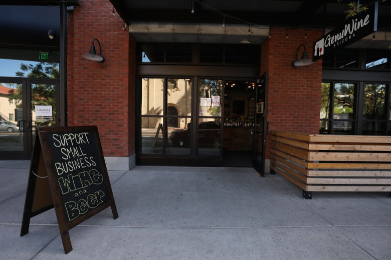 """A sign that reads """"Support Small Business Wine and Beer"""" outside GenuWine Arizona store in Phoenix on March 26"""