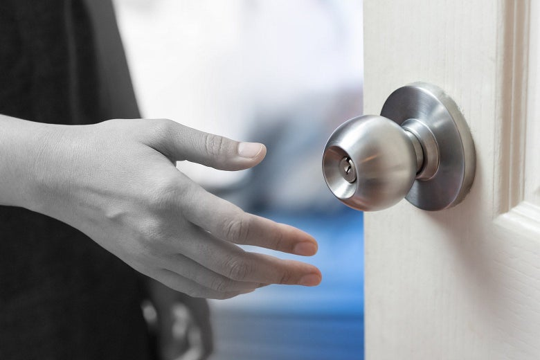 A hand reaching for a doorknob, with half of the image in black and white