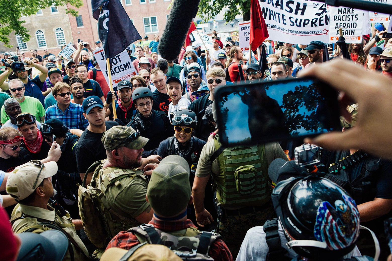 A diverse group of counterprotesters argues with protesters in military gear.