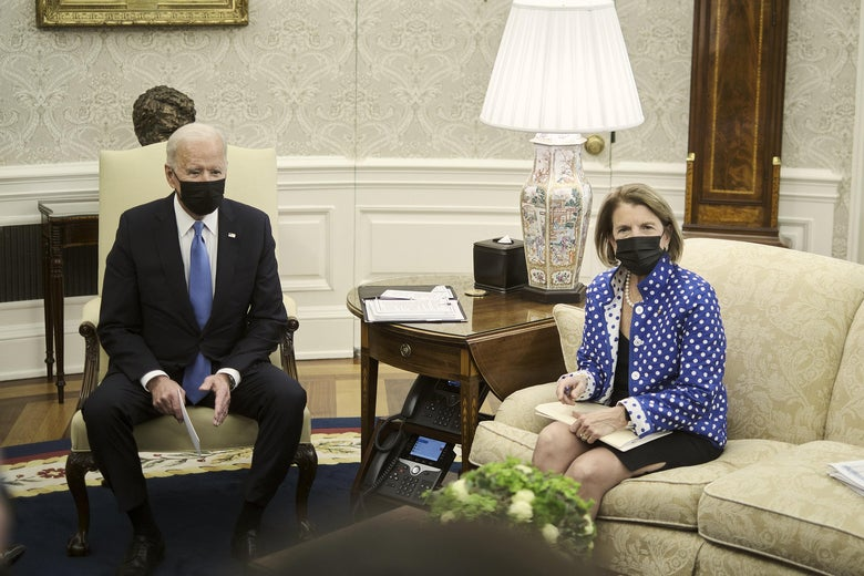 Biden sits in an armchair and Capito on a couch, both wearing black masks, during a meeting