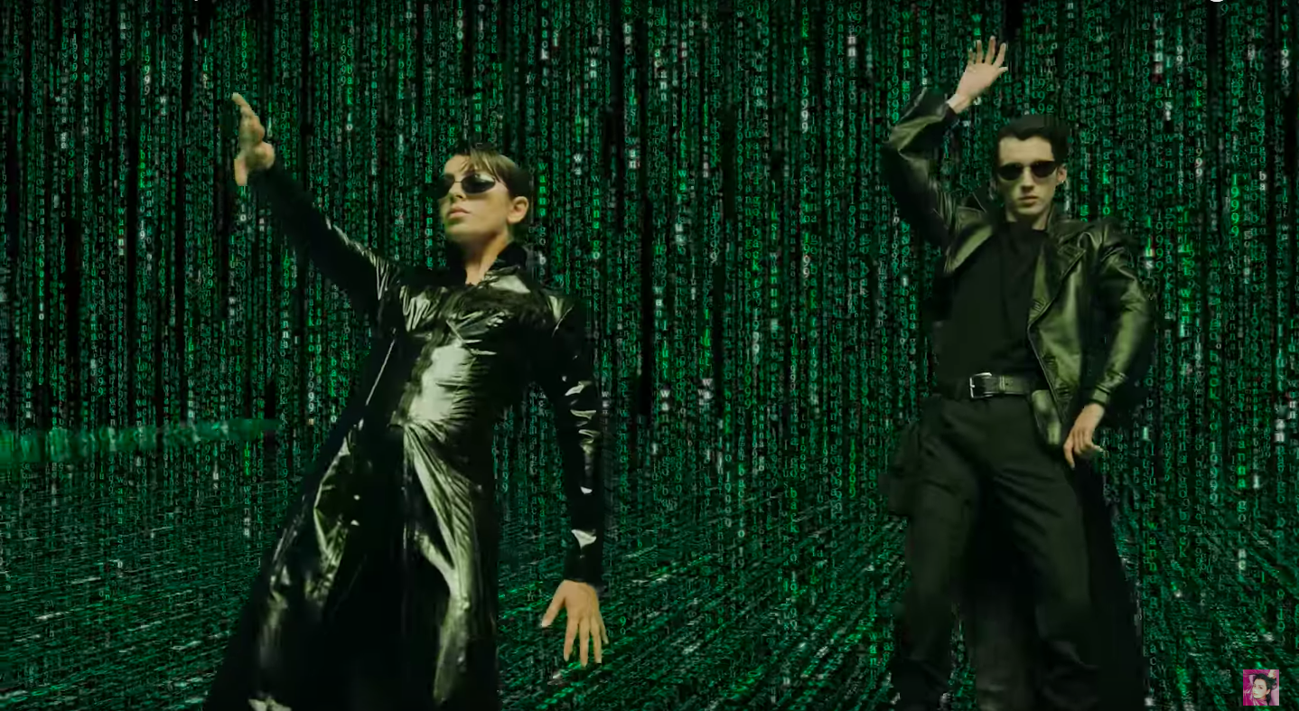 Charli XCX and Troye Sivan wearing all black and leaning back with their hands up, inside a field of green ones and zeros.