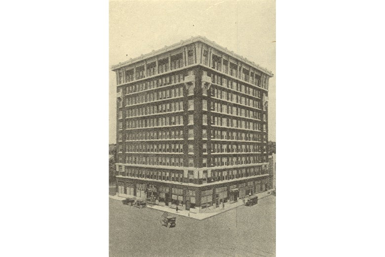 A ten-story brick building in 1916; automobiles are parked out front.