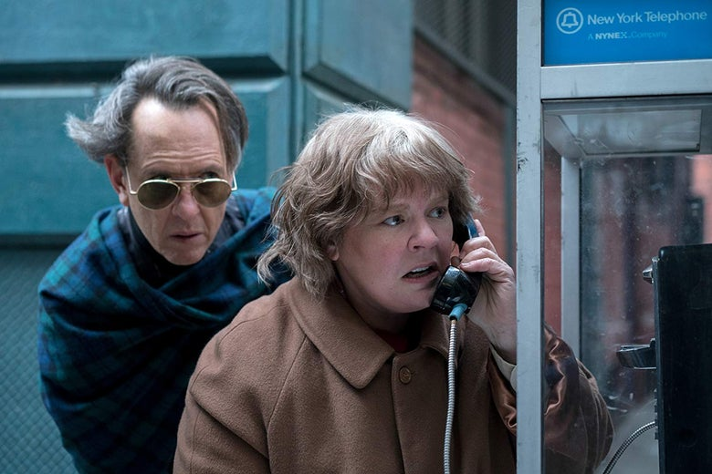 Richard E. Grant stands behind Melissa McCarthy as she uses a payphone.