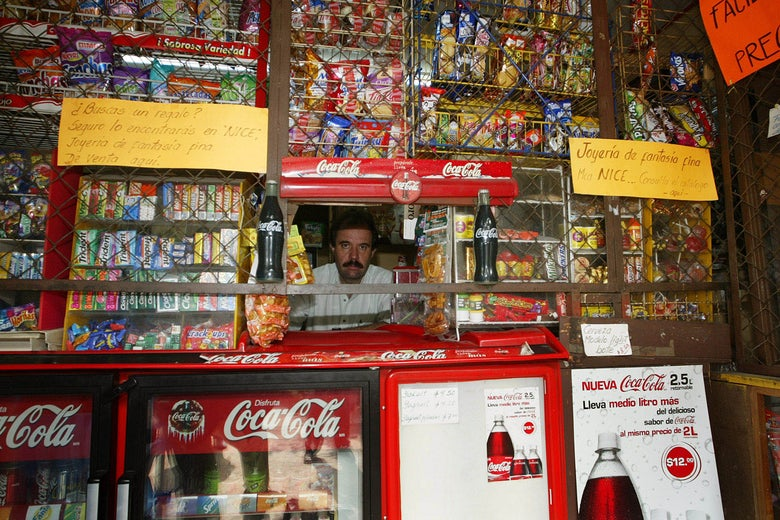 The owner of a convenience store sits behind a wall of junk food.