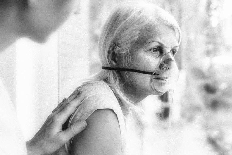 An older woman sits with an oxygen mask on her face while someone mostly out of frame puts a hand on her back.