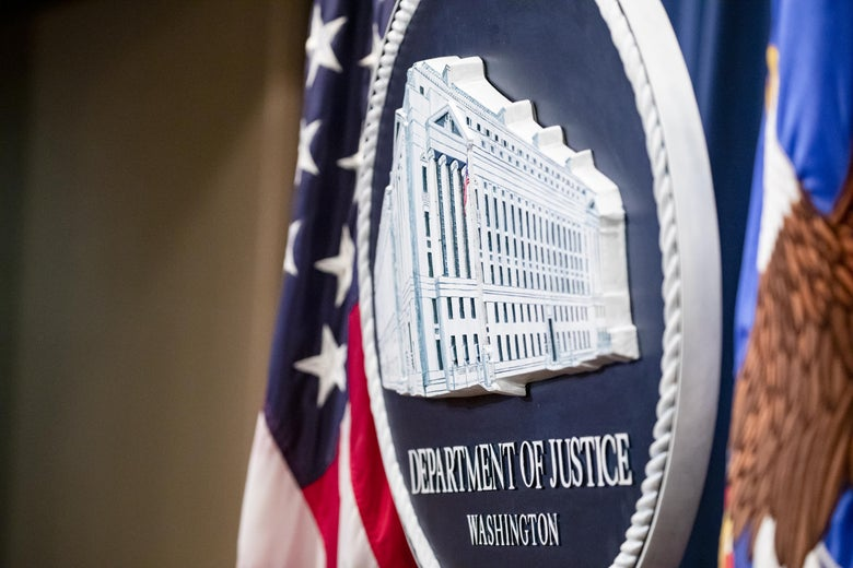 The Justice Department seal, seen at an angle between two U.S. flags