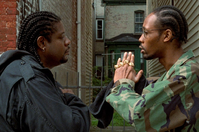 Forrest Whitaker and RZA look at each other, in profile, in a movie still.