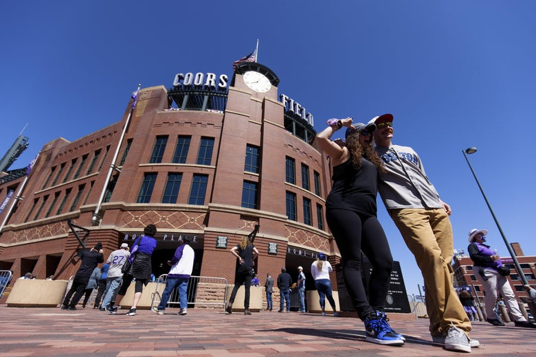 Fans pose outside the stadium ahead of a game on April 1, 2021 in Denver, Colorado.