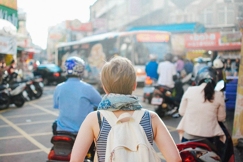 A traveler with a backpack explores an urban street. There are lots of parked motorcycles.